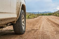 close up of car tire on dirt road